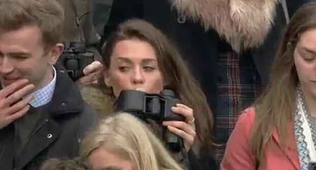 Оператор канала ITV Racing заснял, как девушка быстро оглядывается, откручивает крышку бинокля и осторожно подносит его ко рту