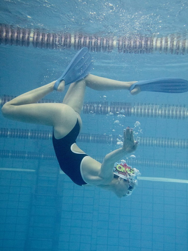 Взгляд с другой стороны водной глади на тренировку в бассейне